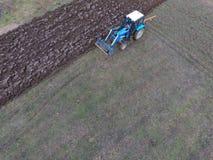 Tractor que ara el jardín Arado del suelo en el jardín Imagen de archivo