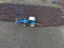 Tractor que ara el jardín Arado del suelo en el jardín Fotos de archivo libres de regalías