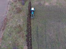 Tractor que ara el jardín Arado del suelo en el jardín Foto de archivo