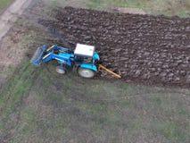 Tractor que ara el jardín Arado del suelo en el jardín Fotografía de archivo libre de regalías