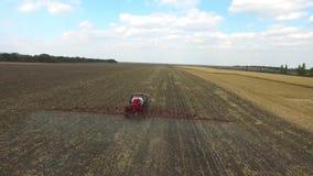 Tractor que ara el maíz de campos en primavera aéreo almacen de metraje de vídeo