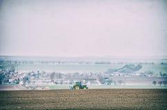 Tractor que ara en el campo, filtro análogo Imagenes de archivo