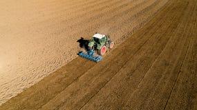 Tractor que ara un campo en el campo francés Imagen de archivo
