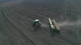 Tractor que cultiva el campo agrícola en la cámara lenta en el tiempo de primavera, visión desde la altura almacen de metraje de vídeo