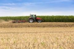 Tractor que cultiva el campo de rastrojo del trigo, residuo de la cosecha Fotos de archivo libres de regalías