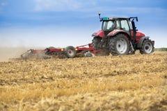 Tractor que cultiva el campo de rastrojo del trigo, residuo de la cosecha Fotos de archivo