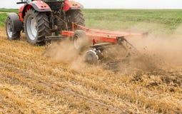 Tractor que cultiva el campo de rastrojo del trigo, residuo de la cosecha Imagenes de archivo