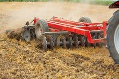 Tractor que cultiva el campo de rastrojo del trigo, residuo de la cosecha Foto de archivo libre de regalías