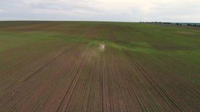 Tractor que cultiva el campo en la primavera, opini?n a?rea de la puesta del sol metrajes