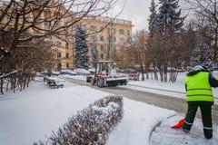 Tractor que limpia el camino de la nieve El excavador limpia el st Imagen de archivo libre de regalías