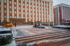 Tractor que limpia el camino de la nieve El excavador limpia el st Fotos de archivo libres de regalías