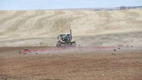 Tractor que prepara la tierra con el cultivador del semillero en tierras de labrant?o Trabajo agr?cola en el proceso, cultivo de  metrajes