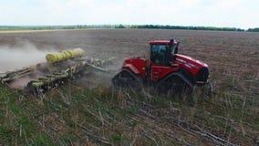 Tractor que prepara la tierra para sembrar diecis?is filas a?reas, el concepto de cultivo, siembra, arando el campo, el tractor y almacen de metraje de vídeo