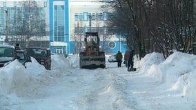 Tractor que rastrilla nieve en la yarda en Rusia en invierno almacen de metraje de vídeo