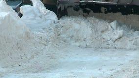 Tractor que rastrilla nieve en la yarda en Rusia en invierno