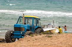 Tractor que recupera un barco del agua que salpica Imagen de archivo