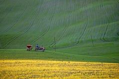 Tractor que trabaja en hierba verde y amarilla Imagenes de archivo