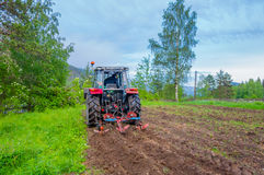 Tractor que trabaja en la abertura del campo que prepara el suelo Imagen de archivo