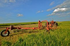 Tractor and Rake Parked in Hay Field. A tractor and rake parked in a prairie hay field are used in the process of making windrows for baling Stock Image