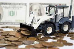 A tractor raking coins. financial Royalty Free Stock Photography