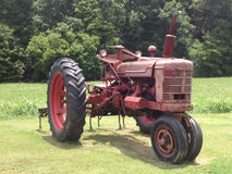 Tractor. A red farm-all tractor with plow Royalty Free Stock Image