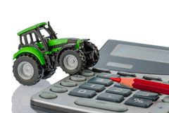 Tractor, red pen and calculator Stock Photos