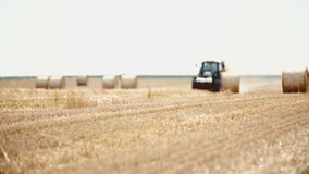 Tractor releases a hay bale, straw. Agriculture background. stock video footage