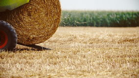 Tractor releases a hay bale, straw. Agriculture background. stock footage