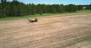 Tractor remolque rojo para las impulsiones de rociadura de las sustancias químicas en campo cosechado almacen de metraje de vídeo