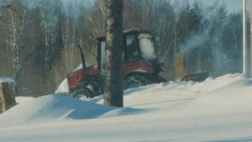 Tractor removing snow from the winter road in the forest. 4K stock video footage