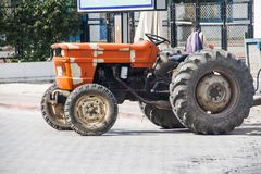 Tractor resting after grueling work. Tractor Orange Work Land Plow Wheels Power Cargo Equipment Farm Village Stock Photo