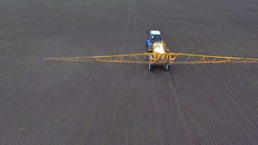 A tractor rides across the field spraying the crop, shooting from the air. stock video footage