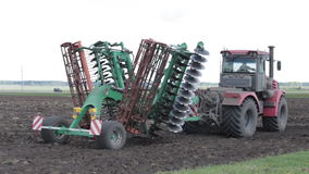 Tractor rides on the field with the system of planting beans stock footage