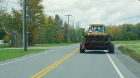 Tractor rides on the road slowly, prevents drive car. New York State, USA. A typical area stock video