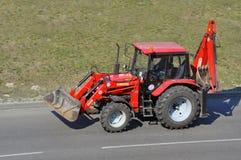 Tractor rojo con los accesorios en el camino imagen de archivo libre de regalías