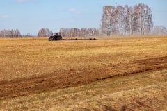 Tractor rojo con una paleta arrastrada para segar y escardar los campos para la agroindustria del color amarillo debajo del cielo imagenes de archivo