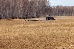 Tractor rojo con una paleta arrastrada para segar y escardar los campos para la agroindustria del color amarillo debajo del cielo imagen de archivo