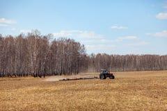 Tractor rojo con una paleta arrastrada para segar y escardar los campos para la agroindustria del color amarillo debajo del cielo fotos de archivo