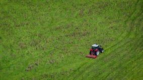 Tractor rojo en campo verde Imágenes de archivo libres de regalías