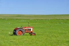 Tractor rojo en la pradera Fotos de archivo libres de regalías