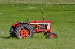 Tractor rojo en la pradera Foto de archivo libre de regalías