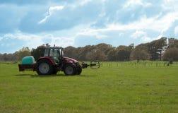 Tractor rojo en un campo Foto de archivo libre de regalías