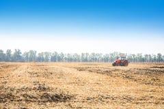 Tractor rojo moderno en el campo Imagen de archivo libre de regalías