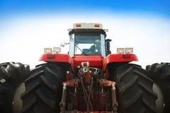 Tractor rojo moderno en un fondo del cielo azul Imagen de archivo libre de regalías