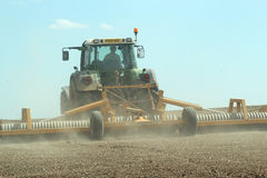 Tractor rolling field on a farm Stock Image