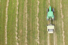 Tractor with round baler - shot from above. Aerial view of tractor with round baler rolling bales of straw on harvested field stock photography