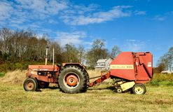 Tractor and Round Hay Baler. This is a Fall picture of and international 784 Tractor and a New Holland 630 Round Hay Baler in a pasture located in Donegal stock photos