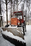 Tractor with scraper in winter day Royalty Free Stock Photo