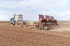 Tractor with seeder, sowing works Royalty Free Stock Photos