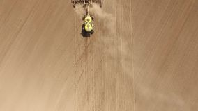 Tractor with a seeder. A tractor with a pneumatic seeder sows a field. The camera flies over the traces of the seeder and overtakes the tractor stock footage